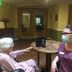 Daystar Retirement Village Keeping Residents Connected During COVID-19 Staff Aiding Resident with Video Call to Family