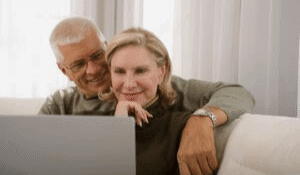 Senior couple sitting on the couch using Facebook together on their laptop