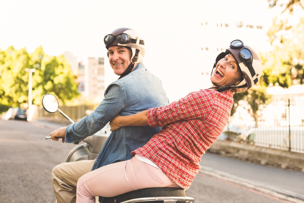 Happy mature couple riding a scooter in the city on a sunny day.jpeg