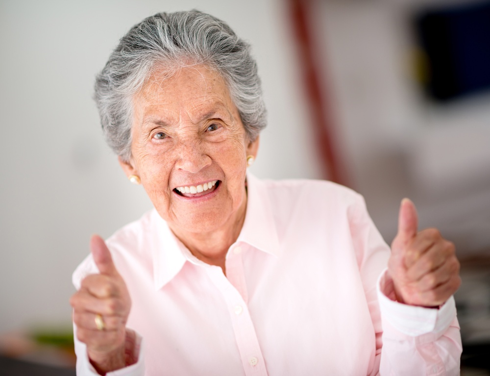 Portrait of a happy senior woman with thumbs up