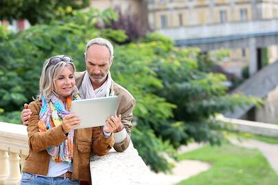Senior tourists looking for information on tablet