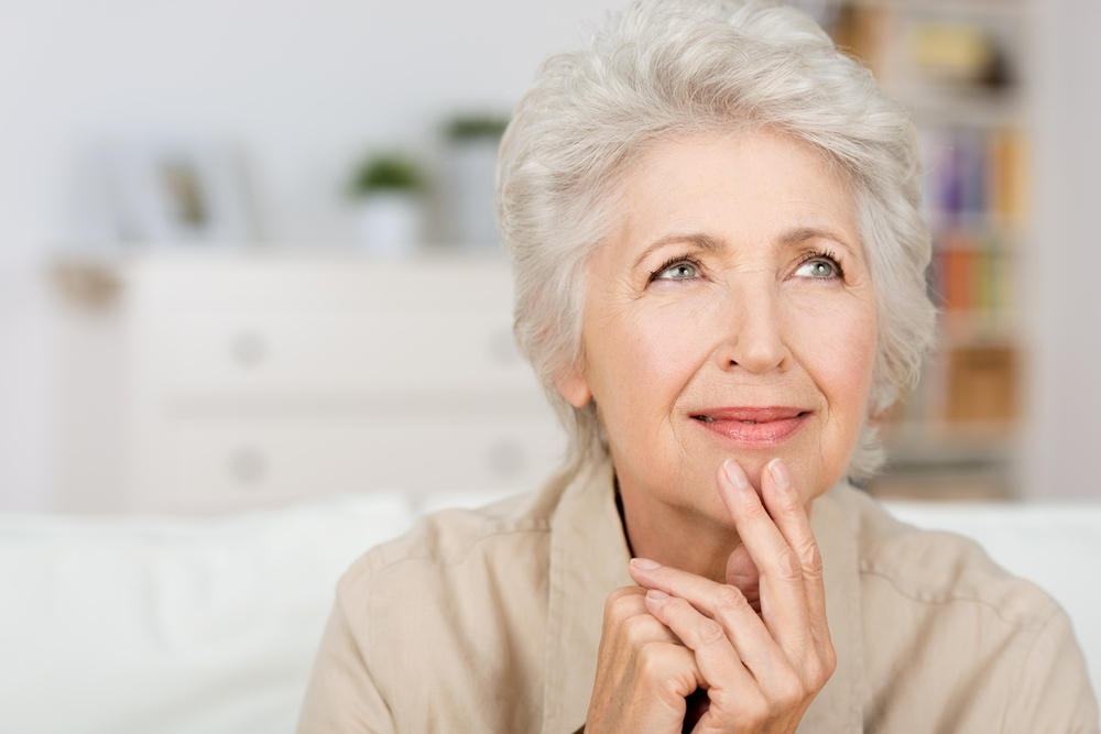 Thoughtful senior lady sitting at home with her fingers to her chin reminiscing and recalling fond memories, close up portrait.jpeg