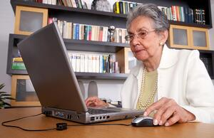 eldery woman on a laptop at home reading the screen-1