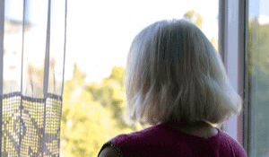 Depressed senior woman staring out the window of her home during daytime