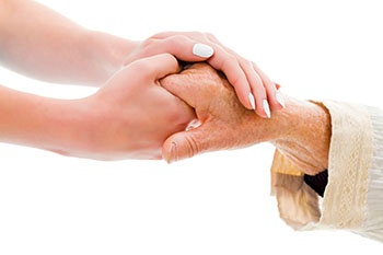 Caregiver holding the hand of the senior she is caring for